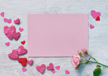 st  valentin: Valentine pink card with valentines heart shaped and pink rose on a white wooden background.
