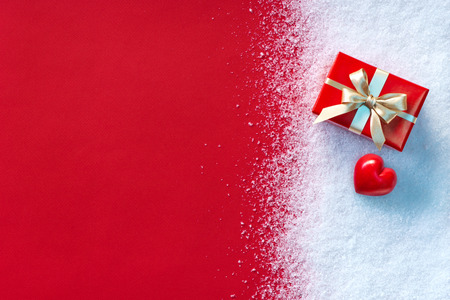 valentines background: Holiday gift and red heart in the snow with red paper background.