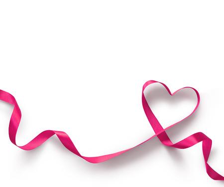 lazo rosa: Corazón rosado de la cinta en el fondo blanco Foto de archivo