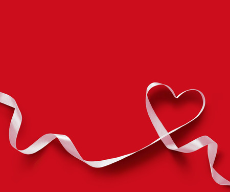curved ribbon: White Ribbon Heart on red background Stock Photo