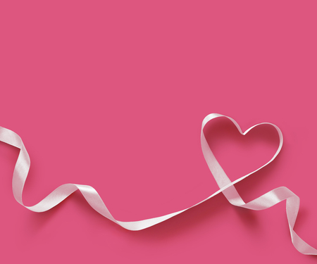 White Ribbon Heart on pink background Archivio Fotografico