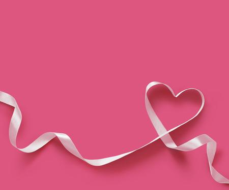 lazo rosa: Corazón de la cinta blanca sobre fondo de color rosa