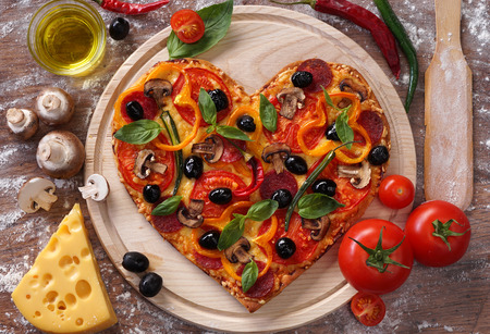 food concept: Pizza heart shape with ingredients on vintage boards.