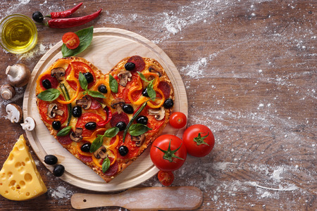 Tasty heart shaped pizza decorated with vegetables and herbs on wooden background.