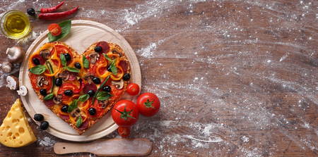 Pizza hartvorm met ingrediënten en een kopie spase op vintage achtergrond. Fijne Valentijnsdag. love concept