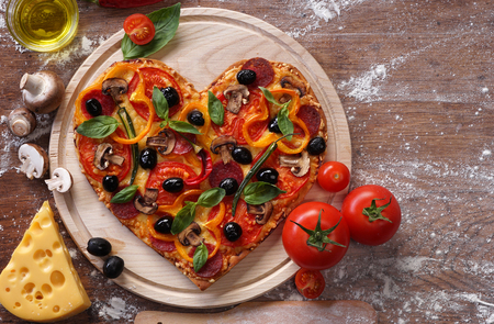 comida italiana: la forma del coraz�n de pizza con los ingredientes en las juntas de la vendimia. Foto de archivo