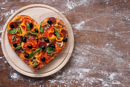 Baked heart-shaped homemade pizza on a cutting board on rustic table, close-up.
