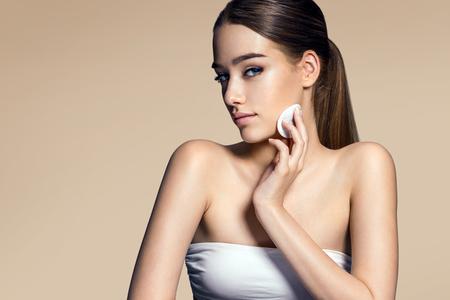 pulizia viso: Giovane donna che applica fondamento sul fronte con il soffio di polvere su fondo beige