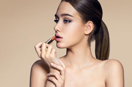 cuerpo femenino perfecto: Mujer joven con el l�piz labial en el fondo beige