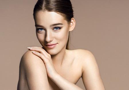 femmes souriantes: fille brune sur fond beige Banque d'images