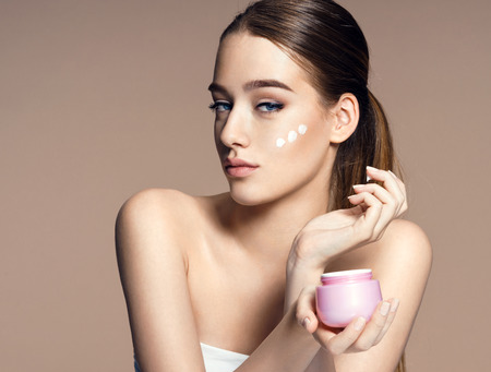 body grooming: Beautiful young woman applying moisturizing creme Stock Photo