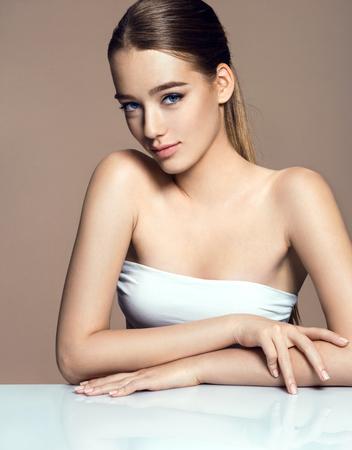 Jonge mooie vrouw met professionele make-up op beige achtergrond