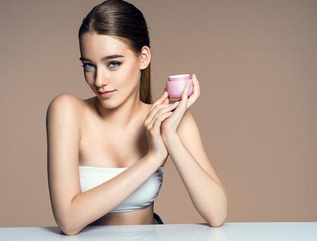 mujer maquillandose: joven y hermosa aplicación de crema hidratante