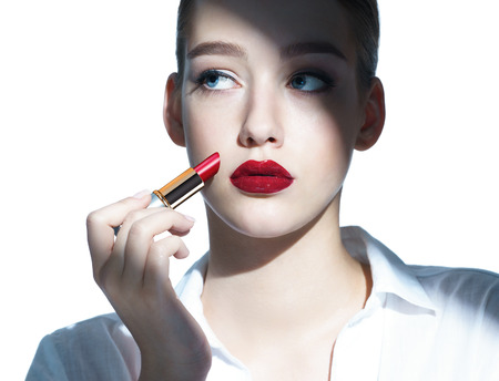mujer maquillandose: Modelo de moda belleza ni�a de aplicar la composici�n l�piz labial rojo de la foto de una ni�a morena - aislado en fondo blanco Foto de archivo