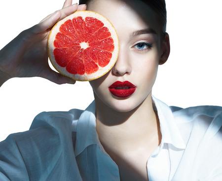 cerrar: Muchacha encantadora con una rodaja de pomelo Foto de archivo