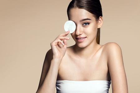 mujer maquillandose: Hermosa mujer morena quitar el maquillaje de la cara