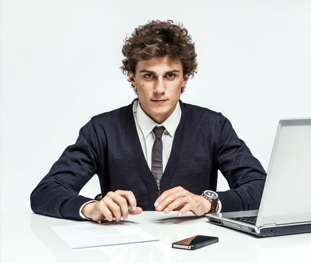 purposeful: Purposeful Manager looking at camera with serious look businessman at the workplace working with computer on gray background, depression and crisis concept