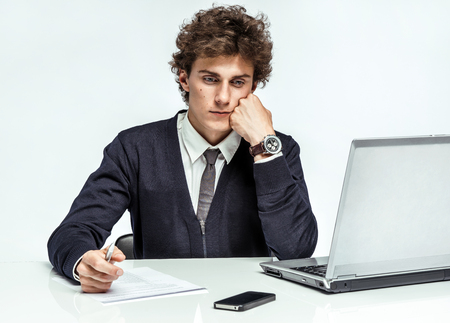 Unhappy entrepreneur dissatisfied with his income, earnings, gain, benefit, margin modern businessman at the workplace working with computer on gray background depression and crisis concept