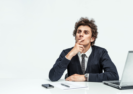 countenance: Pensive businessman looking up with concentration on grey background. Depression and crisis concept Stock Photo