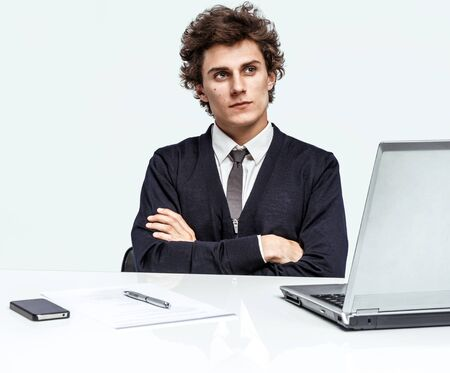 cross armed: Serious businessman with arms across at the workplace in the office and thinking on grey background. Depression and crisis concept