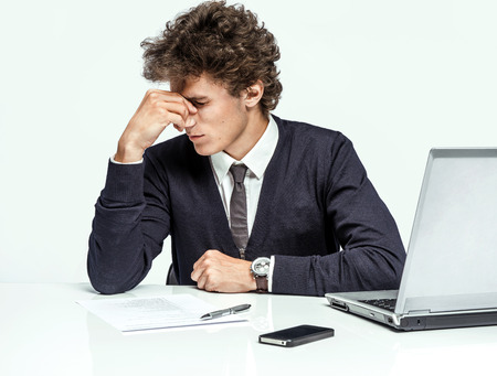 benefit: Overwhelmed Businessman dissatisfied with his earnings, gain, benefit, margin modern businessman at the workplace working with computer on grey background. Depression and crisis concept Stock Photo