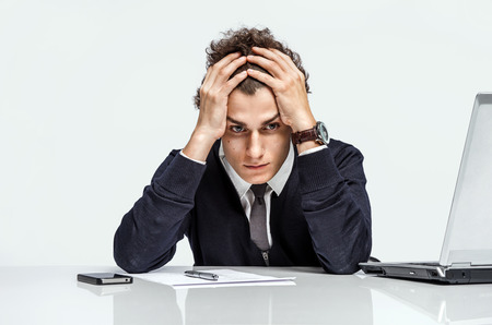 crisis: Entrepreneur dissatisfied with his earnings, profit, income, gain, benefit, margin modern businessman at the workplace working with computer on grey background. Depression and crisis concept