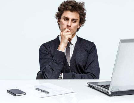 desconfianza: Que duda de negocios sentado en su oficina mientras se lee la información o se ve en una presentación en su ordenador sobre fondo gris. La depresión y la crisis del concepto