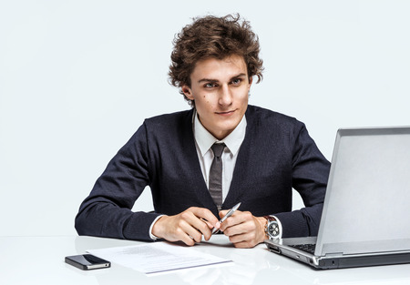 purposeful: Purposeful Manager looking at camera with serious look businessman at the workplace working with computer on gray background