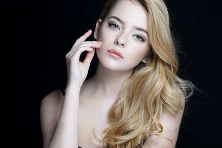 Beautiful young lady with make up face. Close-up of an attractive girl of European appearance on dark background.