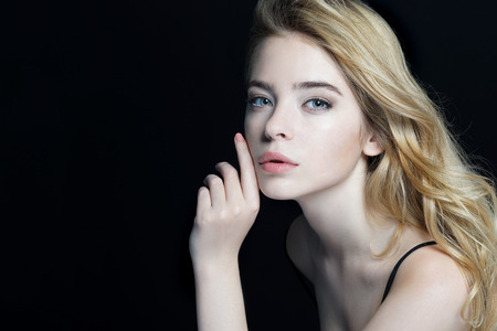 Beautiful Girl face. Perfect skin. Close-up of an attractive girl of European appearance on dark background. Imagens