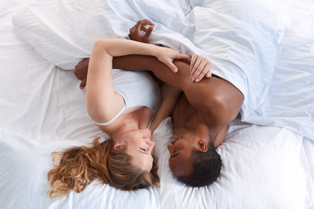 Overhead close up portrait of a young romantic couple hugging. Love and relationships lifestyle, interior bedroom.