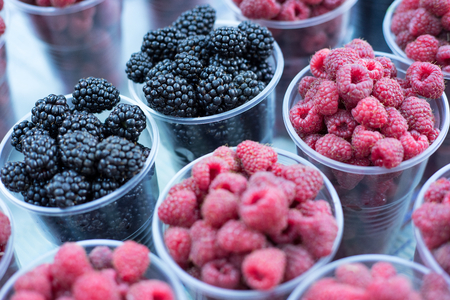 beauteous: Raspberries and blackberry, berry on the table. blackberries and raspberries in bowls, top view, close-up. Selective focus.
