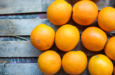 beauteous: Orange fruit on rustic wooden background, oranges on market stall, top view, close-up. Selective focus. Stock Photo