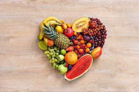 심장 기호입니다. 과일 다이어트 개념입니다. 건강 한 먹는 개념, 나무 테이블에 다른 과일에서 만든 심장의 음식 사진. 높은 해상도 제품.
