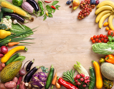 consuming: Fresh vegetables and fruits on wooden table. Top view with copy space