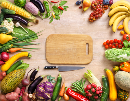 veggies: Healthy food background and Copy space. studio photography of wooden board surrounded by fresh vegetables on wooden table