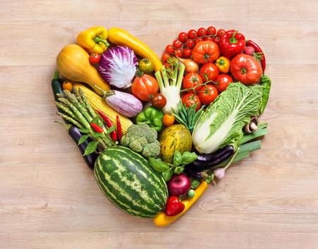 심장 기호. 과일 다이어트 개념입니다. 오래 된 나무 테이블에 다른 과일과 야채로 만든 마음의 건강 먹는 개념 음식 사진
