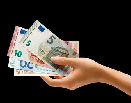 dinero euros: Mano de la mujer que sostiene el dinero aislado en el fondo negro