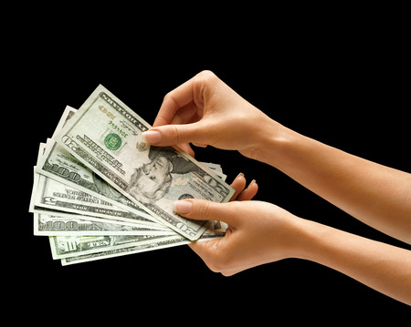 hand with money: Womans hand is giving dollars money isolated on black background Stock Photo