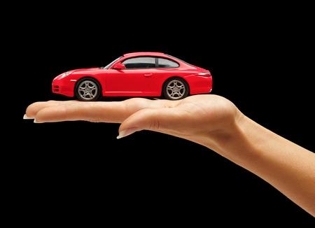 juguete: Mano de la mujer que sostiene un coche de juguete de color rojo aisladas sobre fondo negro
