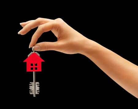 key: Womans hand holding house key with keychain in the form of home isolated on black background Stock Photo