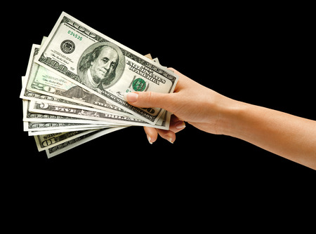 hand with money: Womans hand holding money isolated on black background Stock Photo