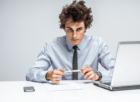 serious businessman: Ambitious young businessman looking at camera with serious look. Businessman at the workplace working, depression and crisis concept