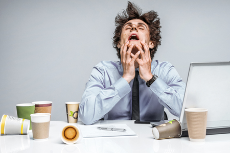 worried businessman: OMG! Frustrated man sitting desperate over paper work at desk. Negative emotion facial expression feeling