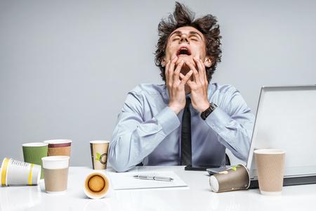 frustrace: PRO BOHA! Frustrovaný člověk sedí zoufalý přes papírování na stole. Negativní emoce mimika pocit