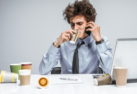 actuary: Coffee and conversation: While talking intensely on a phone, manager sitting with a cup. Modern office man at working place, sloth and laziness concept