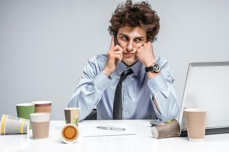 Jonge zakenman praten over de telefoon. Zakenman op de werkplek werken, depressie en crisisconcept Stockfoto