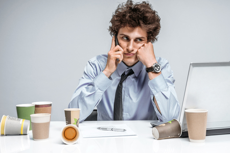 slacker: Young business man talking on the phone. Businessman at the workplace working, depression and crisis concept