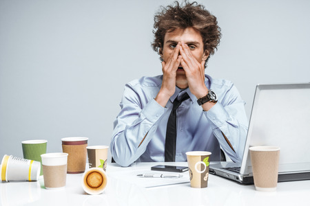 cups of coffee: Exhausted man closed his eyes with his hands. Young student with lot of work, education concept