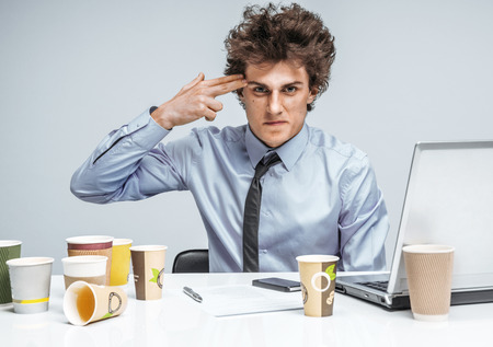 extortion: Young businessman with gun wants to commit suicide  modern office man at working place, depression and crisis concept